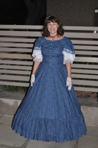 Image of Jenna Barwin in blue calico dress and hoop-lined skirt. Photo accompanies Jenna Barwin biography.