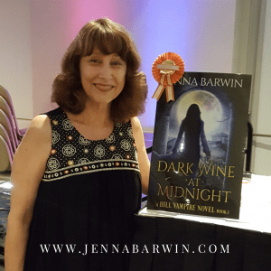 Image of Jenna Barwin standing next to a poster of the book cover for Dark Wine at Midnight, a Hill Vampire Novel Book 1. The cover contains an image of a woman walking through an arched wall, vineyard and full moon. A orange award ribbon is fastened to the poster.